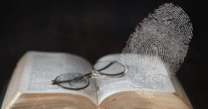 Glasses sitting on top of a Bible, with a large fingerprint in the foreground
